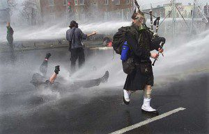 Bagpiper plays next to protestor being hosed