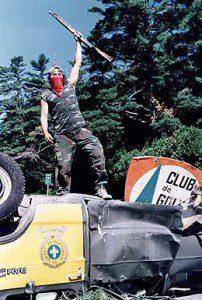 Man holds gun in the air standing on an overturned vehicle, Mohawk warrior Richard Livingston Nicholas