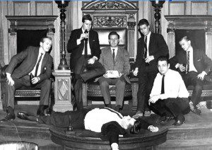 Black and white photo of men in suits with one man playing dead on the ground