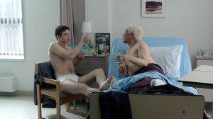 Young man in underwear sits next to bed of elderly man in underwear