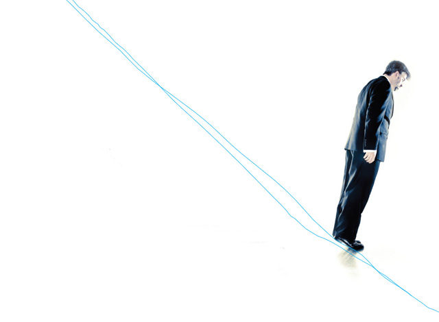 Man in suit standing on string on downward diagonal