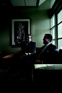 Two men in suits sitting on couch