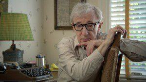Woody Allen sitting in chair by typewriter