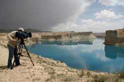 Man taking video of blue lake and canyons with overcast weather