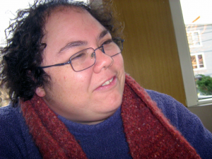 Person with curly hair and glasses