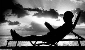 Silhouette of man on reclining chair with book at waterfront with sun going down