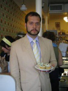 Jesse Brown holds plate of cupcakes wearing a suit