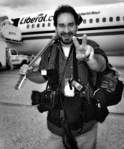 Tom Hanson photographer smiling and holding up peace sign