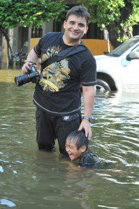 Tibor Krausz with camera knee deep in water next to child shoulder deep in water