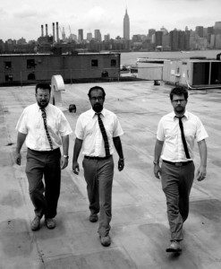Three men in button ups and ties walk on the roof