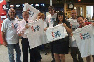 People holding and wearing Chek News shirts