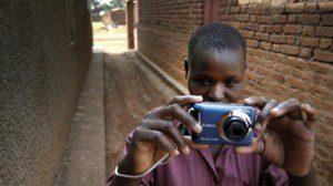 Woman holds camera in brick alleyway