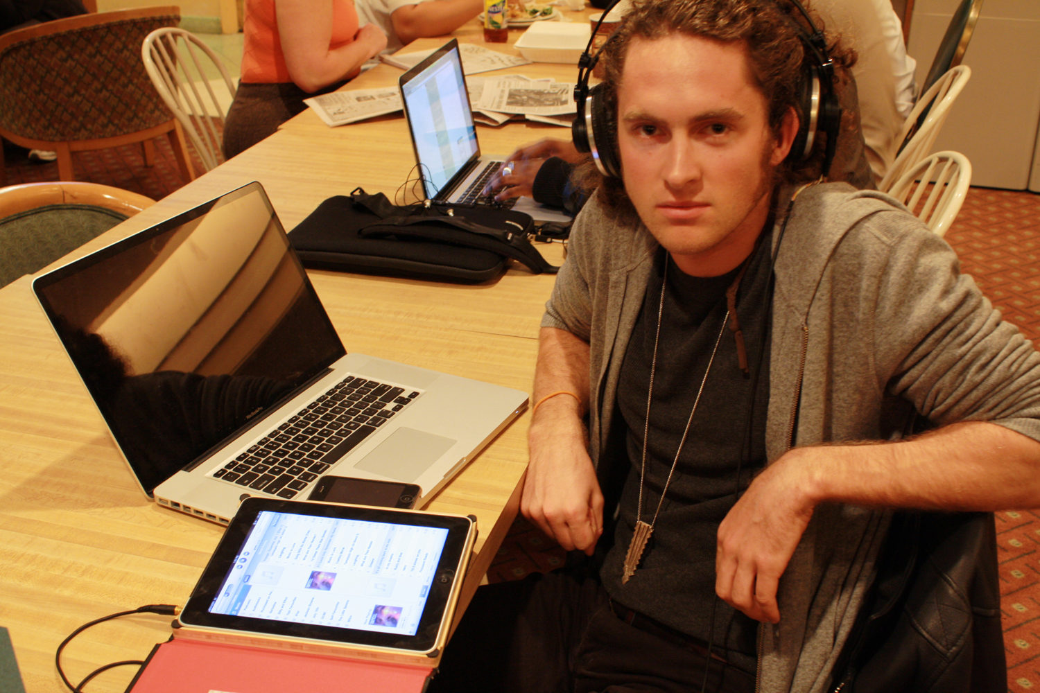Man with headphones on sits next to laptop and ipad