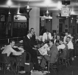 Black and white photo of men at a table, one holds a newspaper