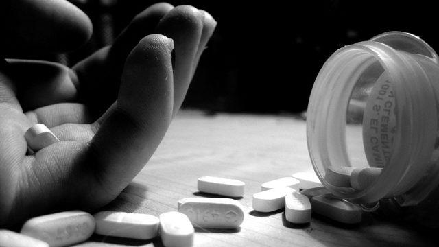 Hand holds pill next to spilled bottle of pills