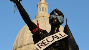 Black statue with bandana over eyes and shoulder with recall sign hanging from neck