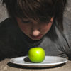 Boy looking at a green apple