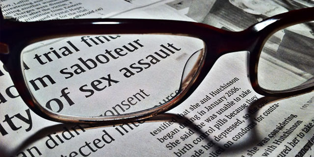 """Eye glasses on news paper page highlighting words """"sex assault"""""""