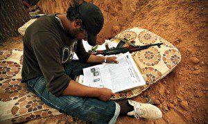 Man in dirt ditch on mattress next to gun reads newspaper