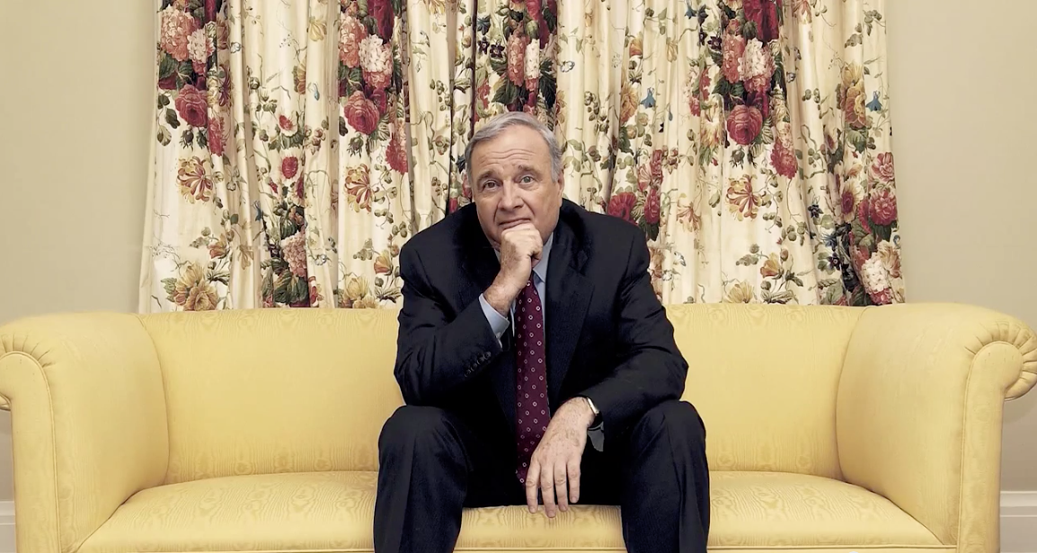 Man in suit on yellow cushion in front of floral curtains