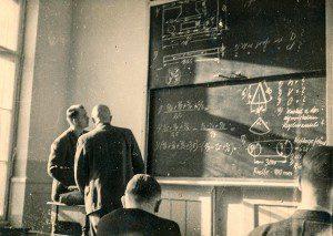 Two men looking at blackboard