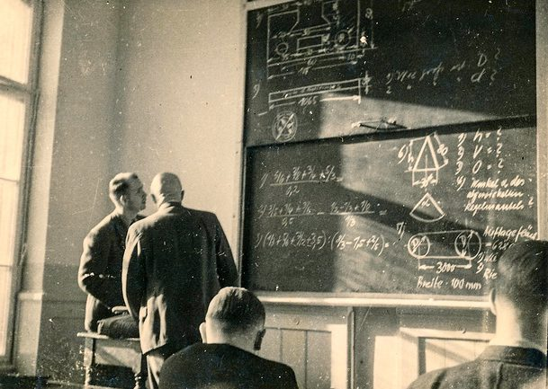 Two men looking at blackboard
