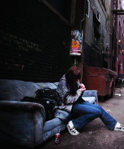 Woman on couch in alley