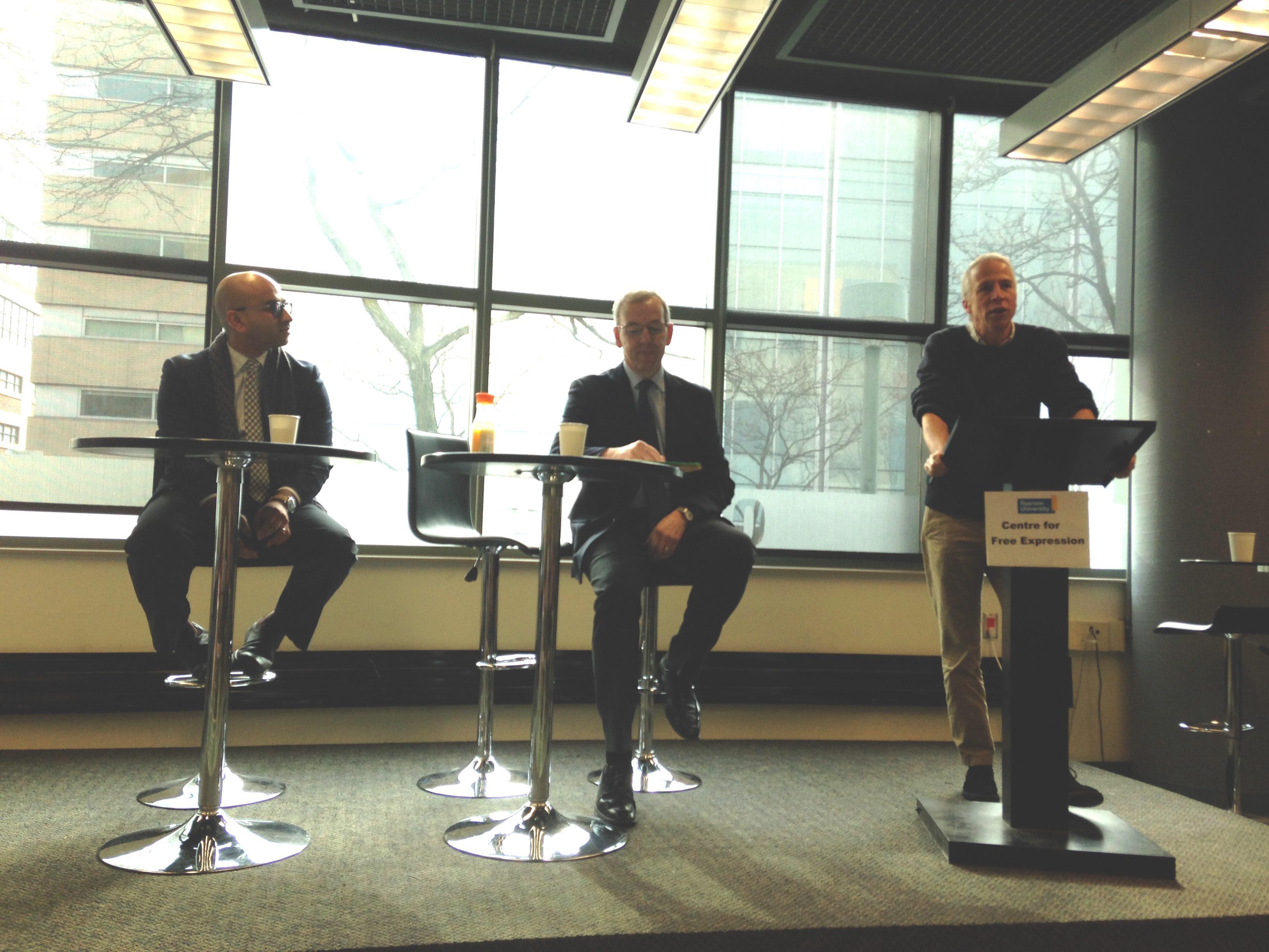 Man at podium next to two men sitting at tables