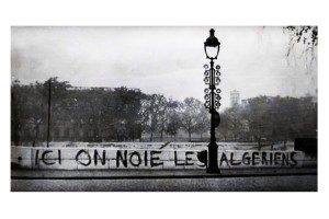 """A screenshot from the documentary """"Ici on noie les Algériens, 17 octobre 1961"""" depicting graffiti on a bridge above the Seine River in Paris reading """"Here we drowned the Algerians."""" Several witnesses reported seeing dead bodies floated in the river after the assault by the police."""