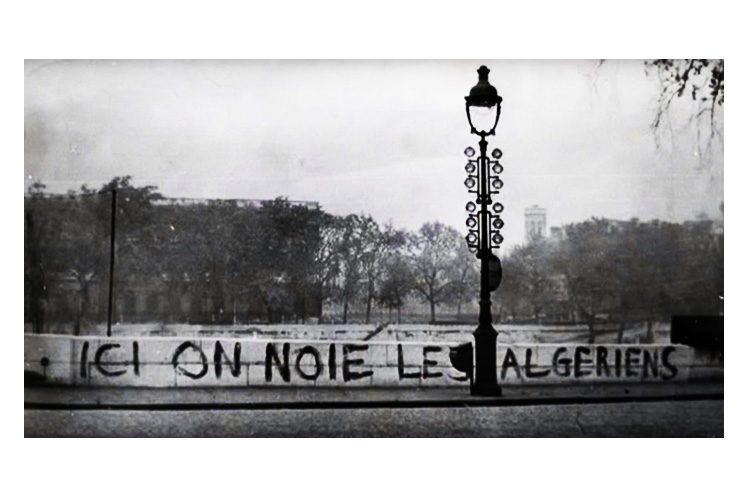 "A screenshot from the documentary ""Ici on noie les Algériens, 17 octobre 1961"" depicting graffiti on a bridge above the Seine River in Paris reading ""Here we drowned the Algerians."" Several witnesses reported seeing dead bodies floated in the river after the assault by the police."