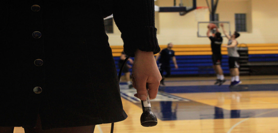 Hand holding a microphone in front of a basketball court