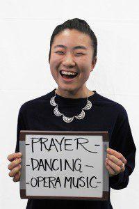 "Woman holds whiteboard ""Prayer, dancing, opera music"""