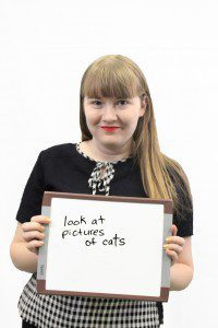 """Woman holds whiteboard """"look at pictures of cats"""""""