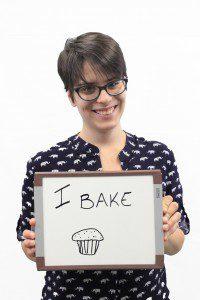 "Woman holds whiteboard ""I bake"""