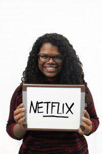 """Woman holds whiteboard """"Netflix"""""""
