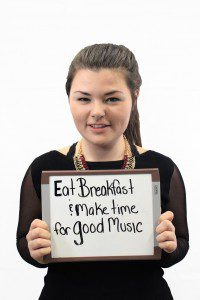 """Woman holds whiteboard """"Eat breakfast and make time for good music"""""""