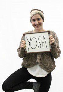 "Woman holds whiteboard ""Yoga"""