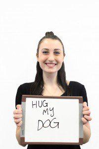 "Woman holds whiteboard ""Hug my dog"""