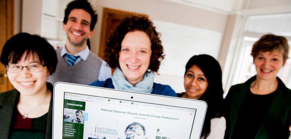 5 people smiling, old holds up Kickstarter page on laptop