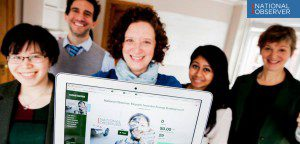5 people smiling, old holds up Kickstarter page on laptop