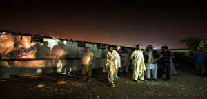 Photos projected on Dubai trailer homes surrounding by onlookers