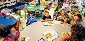 Kids around a school table with a teacher