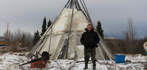 Man stands in front of teepee