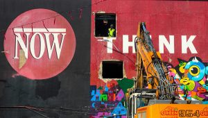 The Now red logo is presented on a black background on one half of the building. On the other side is the painted white word Think on a red background. A construction worker stands in an empty window frame. An excavator is positioned in front of the word Think.
