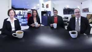Four people at work with coffee cups sitting around a table