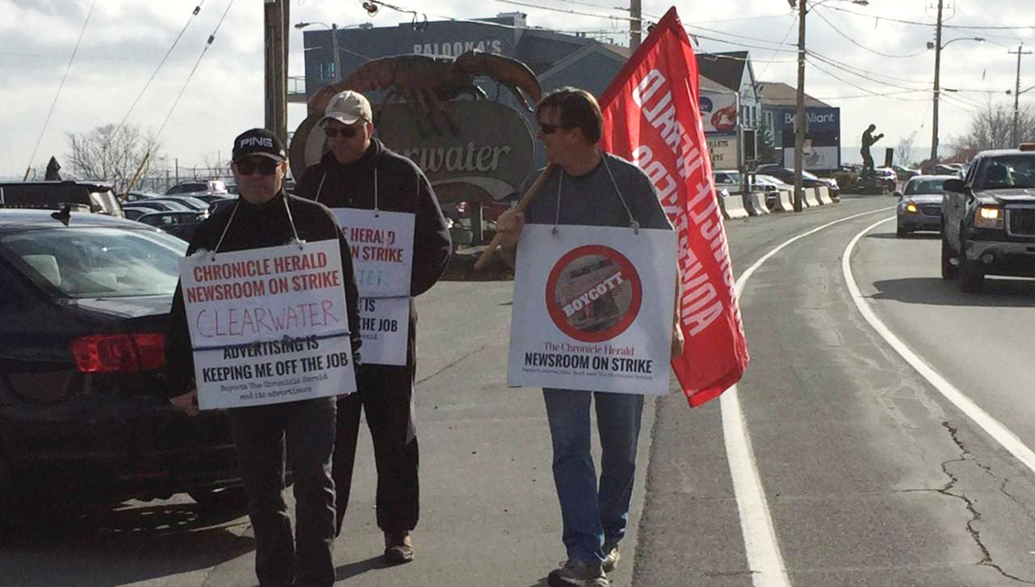 3 strikes from Chronicle Herald with signs and a flag