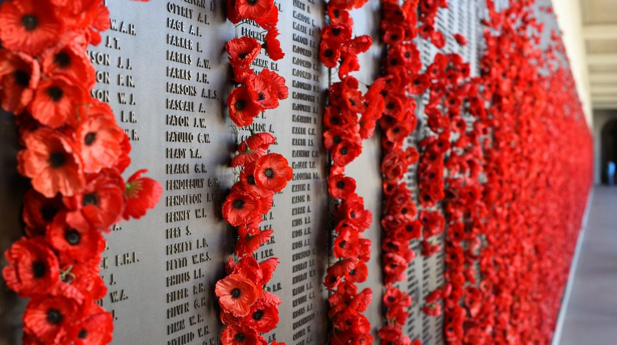 Memorial lists names of lost soldiers and it adorned with poppies