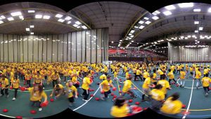 Large number of young people in yellow t-shirts playing with balls