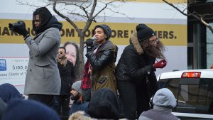 3 protestors at a rally against Trump, one of them Yusra Khogali, co-founder of Black Lives Matter