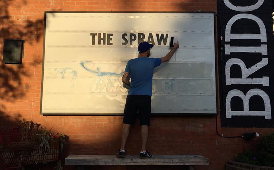 "Jeremy Klaszus places letters spelling ""The Sprawl"" on a billboard"